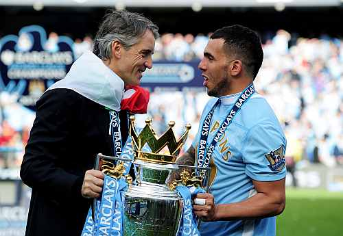 Roberto Mancini the manager of Manchester City and Carlos Tevez of Manchester City celebrate with the EPL trophy