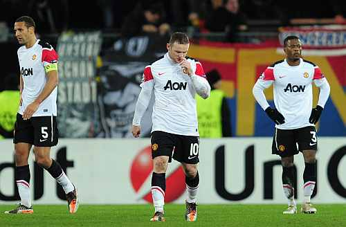 Manchester United players walk off the pitch after their loss against FC Basel