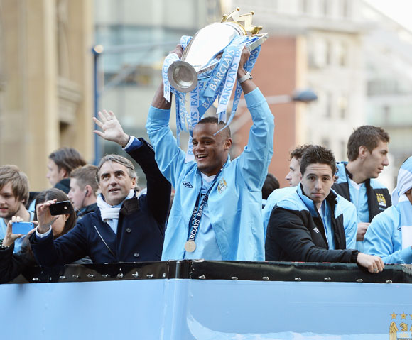 Roberto Mancini the manager of Manchester City stands alongside his captain, Vincent Kompany (C) and Samir Nasri (R) as they parade the Barclays Premier League trophy in front of thousands of fans during their victory parade around the streets of Mancheste