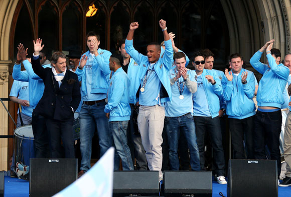 The players of Manchester City wave to their supporters outside Manchester Town Hall as they leave for the start of their victory parade around the streets of Manchester on May 14