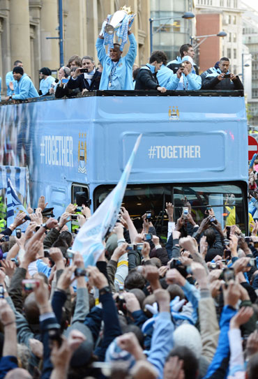 Manchester City captain Vincent Kompany (C) hows off the Barclays Premier League trophy in front of thousands of fans during their victory parade around the streets of Manchester