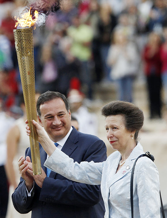 Britain's Princess Anne raises a torch with the Olympic Flame next to Spyros Kapralos, head of the Greek Olympic Committee, during an Olympic flame handover ceremony at the Panathenaic stadium on Thursday
