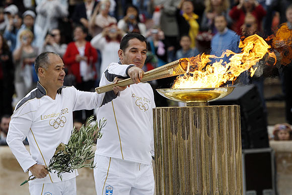 Greek veteran weighlifter Piros Dimas (right) and Chinese gymnast Li Ning light a cauldron with the Olympic Flame inside the marble Panathenaic stadium in Athens on Thursday