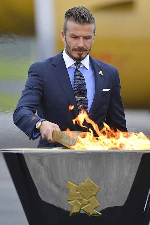 British soccer player and London 2012 Olympic Games ambassador David Beckham lights the Olympic torch with a cauldron after arriving at RNAS Culdrose base near Helston
