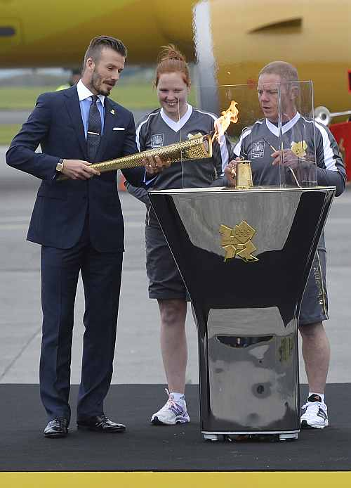 British soccer player and London 2012 Olympic Games ambassador David Beckham reacts after lighting the Olympic torch with a cauldron