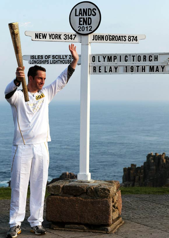 Olympic gold medal sailor and the first London 2012 torchbearer, Ben Ainslee, poses for a photograph beside the Lands End sign.