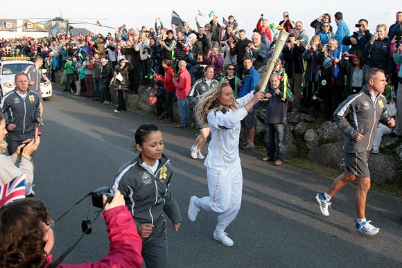 Surfer Tassy Swallow carries the Olympic Flame as it leaves Lands End