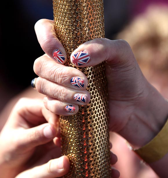 The finger nails of Olympic Flame torchbearer Sarah Blight are decorated in a Union Jack design as she poses for photographs in front of St Michael's Mount