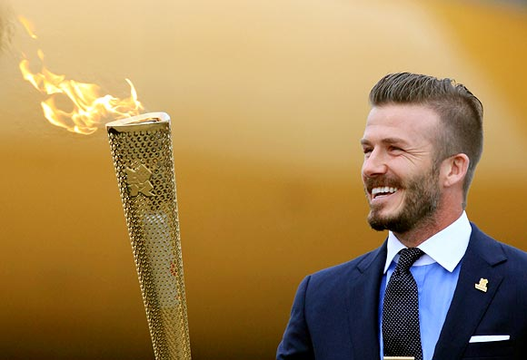 David Beckham holds the Olympic Flame as it arrives at RNAS Culdrose near Helston