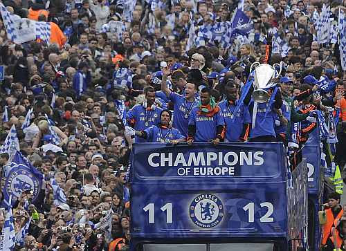 Chelsea football players returning from their Champions League final victory against Bayern Munich are surrounded by fans during a victory parade along the Kings Road in Chelsea