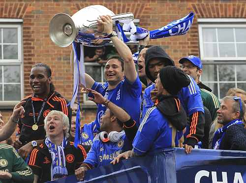 Chelsea's Frank Lampard holds the Champions League trophy near owner Roman Abramovich during their victory parade in west London