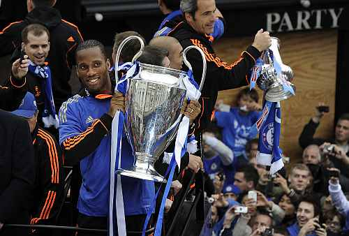Chelsea football player Didier Drogba holds the Champions League trophy during a victory parade along the Kings Road in Chelsea
