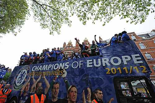 The Chelsea team celebrate from an open top bus during the Chelsea victory parade following their UEFA Champions League and FA Cup victories