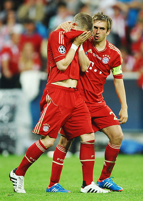 Bastian Schweinsteiger of Bayern Muenchen is comforted by Philipp Lahm