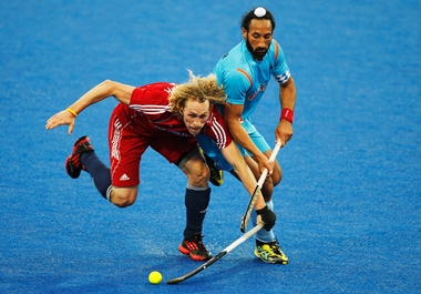 Sardar Singh tackles Richard Alexander of Great Britain on the blue turf during the Olympics test event in London