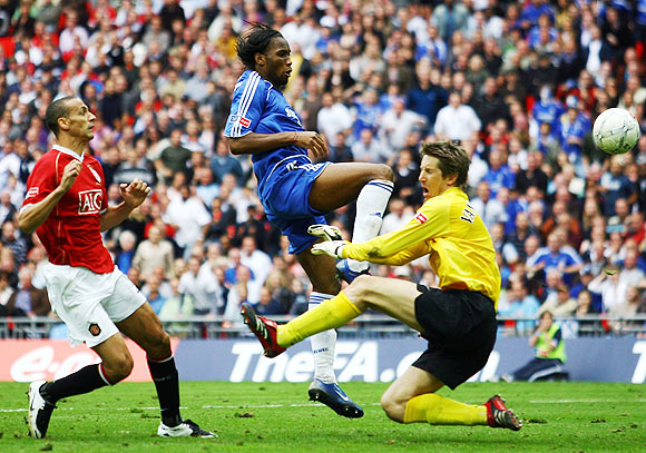 Didier Drogba of Chelsea beats Edwin Van der Sar of Manchester United to score their first goal during the FA Cup Final match