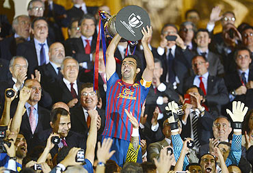Barcelona's Xavi Hernandez lifts up the Spanish King's Cup trophy after winning their final against Athletic Bilbao