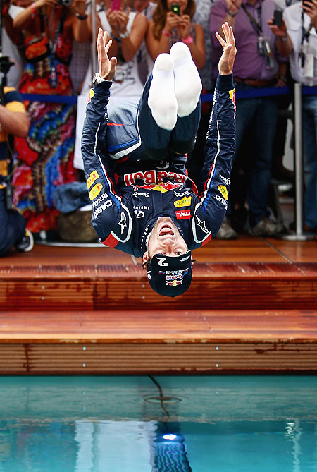 Mark Webber of Red Bull Racing celebrates winning the race by jumping into the swimming pool on the Red Bull Energy Station following the Monaco Formula One Grand Prix