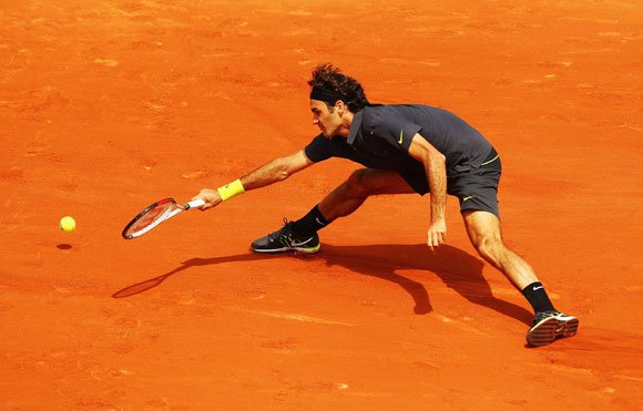 Roger Federer of Switzerland reaches for a forehand during his men's singles second round match against Adrian Ungur of Romania during day four of the French Open at Roland Garros in Paris