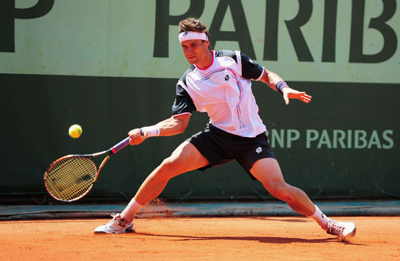 David Ferrer of Spain slides to play a forehand in the men's singles first round match against Lukas Lacko of Slovakia