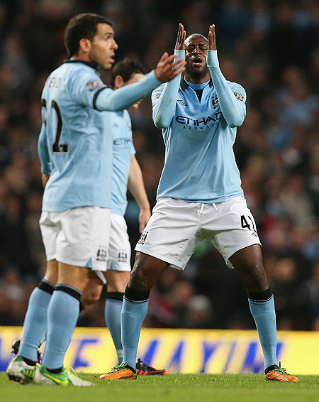aya Toure of Manchester City shows his frustration as Carlos Tevez watches