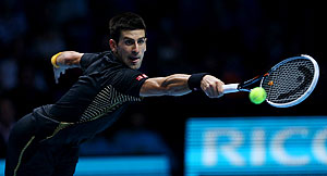 Novak Djokovic returns a shot against Juan Martin Del Potro during their men's singles semi-final of the ATP World Tour finals on Sunday
