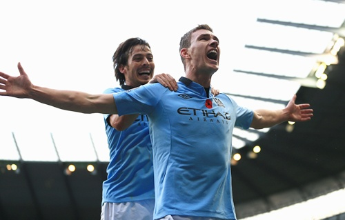 Edin Dzeko of Manchester City celebrates scoring his team's second goal with team-mate David Silva (left)