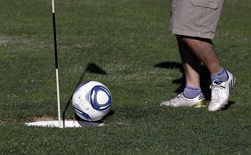 A man kicks a ball into the hole as he competes in a FootGolf tournament