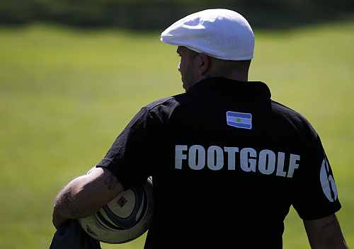 A man carries his soccer ball as he waits for his turn to compete in a FootGolf tournament