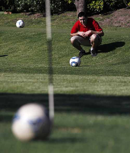 A player lines up a putt as he competes in a FootGolf tournament