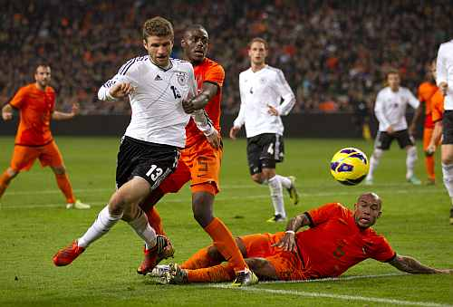 Thomas Mueller of Germany (L) fights for the ball with Bruno Martens Indi (C) and Nigel de Jong