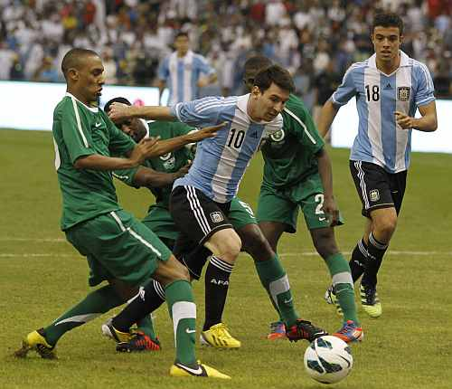 Argentina's Lionel Messi (C) challenges Saudi Arabia's Bader Alnakly (L) for the ball during their friendly soccer match