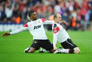 Wayne Rooney of Manchester with teammate Patrice Evra (left)