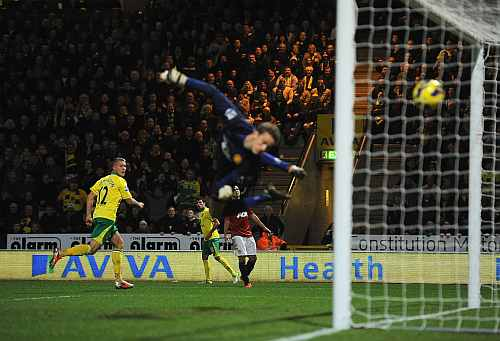 Anthony Pilkington of Norwich City scores his opening goal past goalkeeper Anders Lindegaard of Manchester United during the Barclays Premier League match
