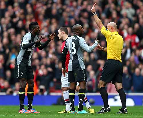 William Gallas protests to referee Howard Webb as team-mate Emmanuel Adebayor of Tottenham Hotspur (L) is shown a red card