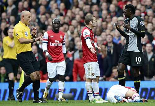Arsenal's Jack Wilshire (3rd L) argues with Tottenham Hotspur's Emmanuel Adebayor (R) as Santi Garzola lies on the ground