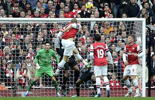 Arsenal's Per Mertesacker (C) rises above the Tottenham Hotspur's defence to score during their English Premier League soccer match