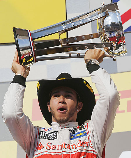 McLaren's Lewis Hamilton holds up his trophy on the podium after winning the US F1 Grand Prix at the Circuit of the Americas in Austin, Texas on Sunday