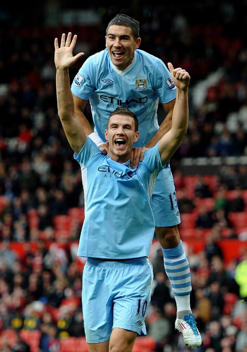 Edin Dzeko of Manchester City celebrates scoring his team's sixth goal with team mate Aleksandar Kolarov during the Barclays Premier League match between Manchester United