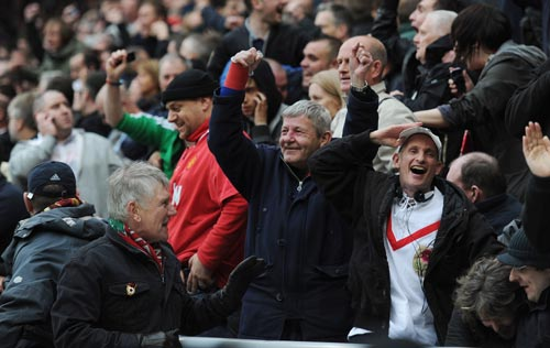 Manchester United fans celebrate hearing news of a goal by QPR at Manchester City during the Barclays Premier League match between Sunderland and Manchester United