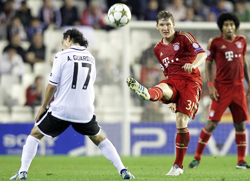 Bayern Munich's Bastian Schweinsteiger (right) kicks the ball past Valencia's Andres Guardado