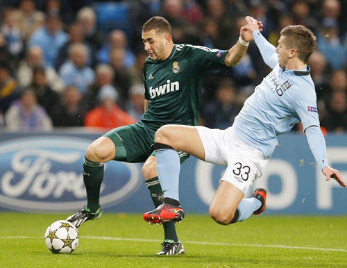 Manchester City's Matija Nastasic (right) challenges Real Madrid's Karim Benzema