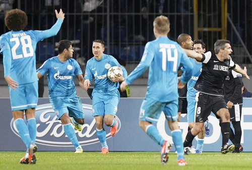 Zenit St. Petersburg's players celebrate after scoring their second goal, while Malaga's Jeremy Toulalan (right) addresses an assistant referee