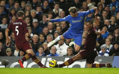 Chelsea's Fernando Torres (C) is tackled by Manchester City's Pablo Zabaleta (L) and Vincent Kompany during their English Premier League soccer match