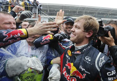 Red Bull Formula One driver Sebastian Vettel of Germany (R) celebrates winning the world championship with his team after finishing sixth in the Brazilian F1 GP