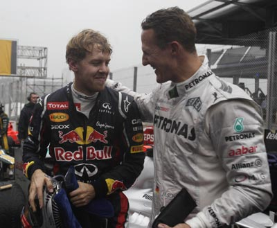 Mercedes Formula One driver Michael Schumacher of Germany (R) congratulates compatriot Red Bull driver Sebastian Vettel after the Brazilian F1 Grand Prix