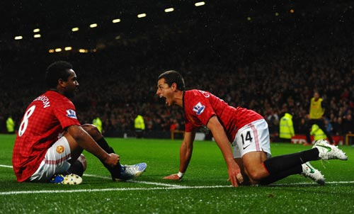Javier Hernandez of Manchester United celebrates scoring his team's third goal with team-mate Anderson (L) to make the score 3-1 during the Barclays Premier League match between Manchester Unite