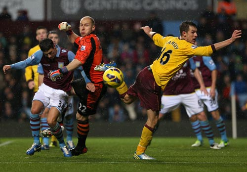 Goalkeeper Bradley Guzan of Aston Villa clears the ball ahead of Aaron Ramsey of Arsenal during the Barclays Premier League match between Aston Villa and Arsenal