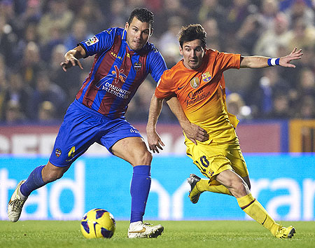 David Navarro (left) of Levante and Lionel Messi of Barcelona vie for possession during their la Liga match on Sunday