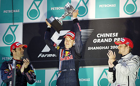 Red Bull's Sebastian Vettel (centre) celebrates with his trophy after winning the Chinese F1 Grand Prix in Shanghai on April 19, 2009